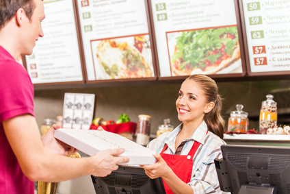 Restaurant worker serving food with smile. woman holding box with pizza at fast food restaurant
